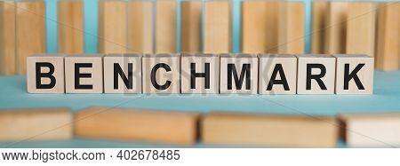 Benchmark Word Written On Wooden Blocks On Light Blue Background.