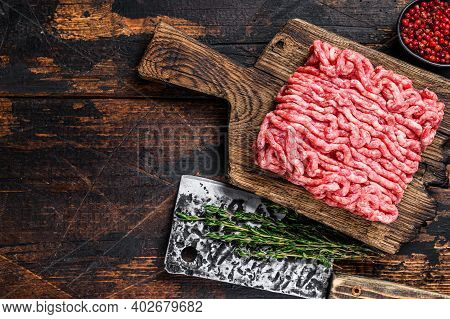 Raw Mince Beef, Ground Meat With Herbs And On A Wooden Cutting Board. Dark Wooden Background. Top Vi