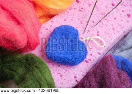 Hearts Made Of Wool, Needles For Felting, A Sponge And Skeins Of Wool On The Table, The Process Of F