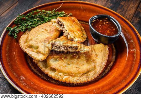 Fried Empanadas With Minced Beef Meat Served On A Plate With Chili Sauce. Dark Wooden Background. To