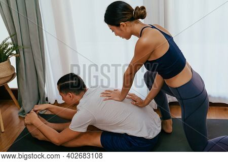 Young Woman Helping Man Stretch Out While Practicing Yoga In Living Room. Couple Working Out At Home