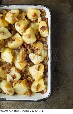 Close Up Of A Tray Of Rustic Baked Potatoes And Bacon