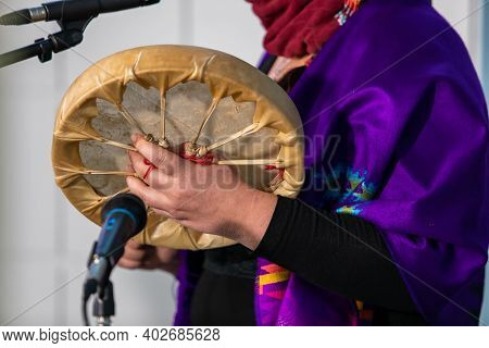 Sound Demonstration During A Native Drum Workshop. Woman In Colored Native Scarf Holing A Sand Made