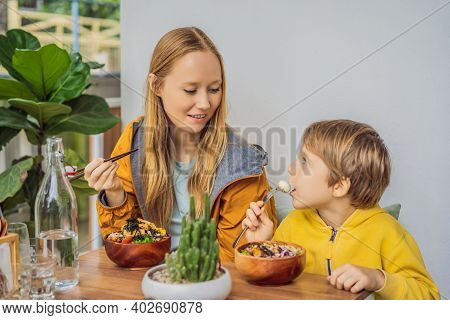 Mother And Son Eating Raw Organic Poke Bowl With Rice And Veggies Close-up On The Table. Top View Fr