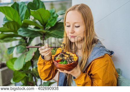 Woman Eating Raw Organic Poke Bowl With Rice And Veggies Close-up On The Table. Top View From Above