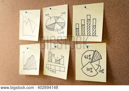 Different Business Graph Charts On Yellow Sticky Notes For Business Planning Review Or Marketing Res