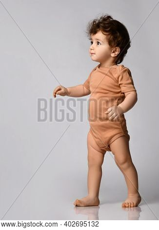Cute Curly-haired Kid In A Beige Body Is Taking Its First Steps, With Ineteresmo Looking Up Against