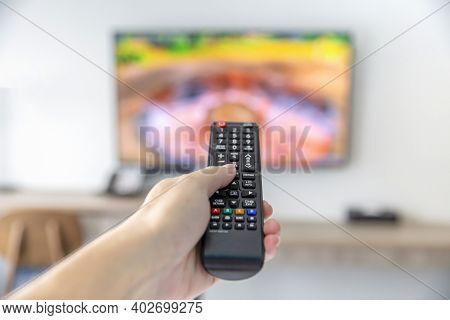 The Man With The Remote Control Watching Tv And Using Remote Controller And Presses The Button
