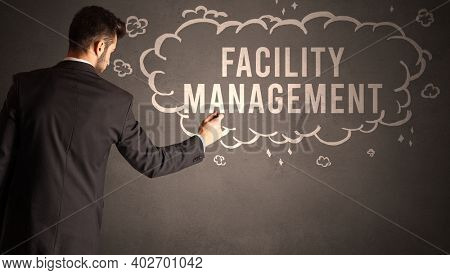 businessman drawing a cloud with FACILITY MANAGEMENT inscription inside, modern business concept