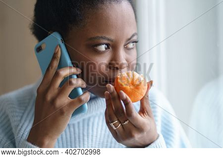 Sick Afro Woman Trying To Sense Smell Of Half Fresh Tangerine Orange, Talking On Phone, Has Symptoms