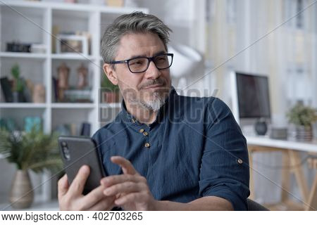 Happy white older man using phone, talking on video chat at home. Conference call with friend, family or work. Reading social media.