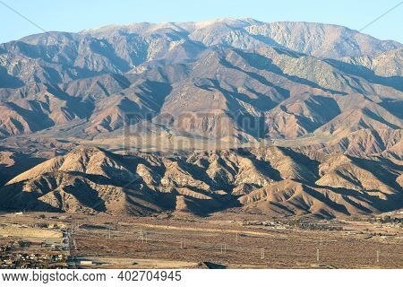 Arid Badlands With Rugged Mountains Beyond During Sunset Creating Natural Shadows Taken In Mt San Go