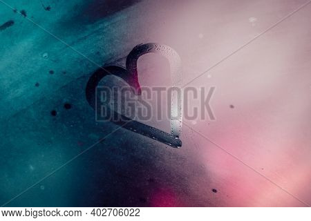 Misted Glass with Drawing Heart on It. Abstract Blurry Pink and Blue Background. Valentine Day Greeting Card. Love Concept.