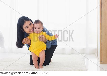 Asian Little Baby Taking First Steps Learning To Walk With Mother Help Support The Cute Unstable Wal