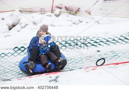 Family Having Fun On Snow Tube. Mother With Kid Is Riding A Tubing. People Sliding Downhill On Tube