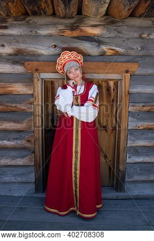 Portrait Of Girl In Russian Authentic Red Clothes On Wooden Background