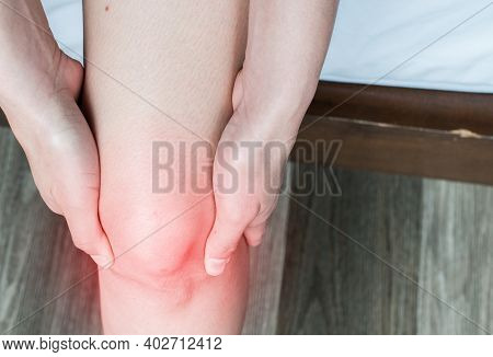 Closeup Of Woman Hands Holding And Massage Her Knee, Suffering From Knee Pain. Knee Pain May Be The