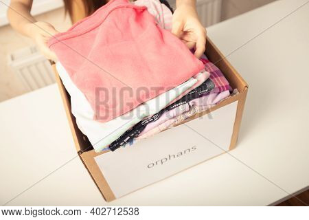 Charity And Assistance To People In Need. Girl Puts Clothes In A Box For Poor Orphans