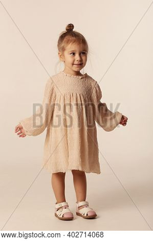 Cute Little Blond Baby Girl In Ivory Color Dress Full Body Portrait