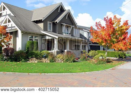 Traditional Canadian house with a large front yard. Beautiful new home with a cozy porch in autumn.