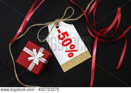 On A Black Background Among A Red Ribbon And A Red Gift Box There Is A Sale Tag That Says Minus Fift