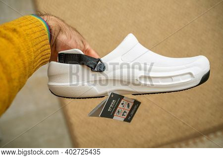 Paris, France - Dec 13, 2020: Pov Male Hnd Holding Side View Against Rug Background Crocs At Work Co