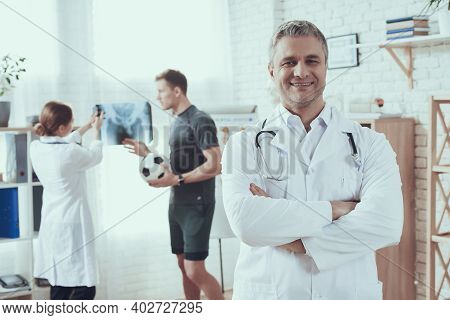 Male And Female Doctors With Stethoscopes In Office. Doctor Is Showing X-ray To Sportsman.