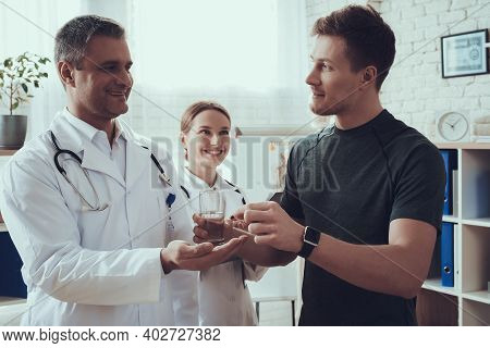 Male And Female Doctors With Stethoscopes In Office. Male Doctor Is Giving Pills To Sportsman.