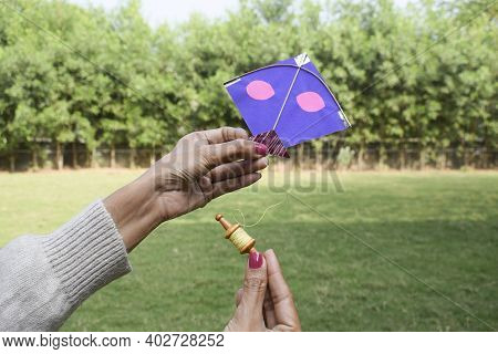Female, Woman, Girl Flying A Miniature Toy Kite With Miniature Cute Toy Spool Manjha In Park. On Occ