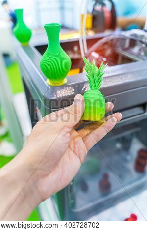 hand with shape of pineapple closeup object printed 3d printer close-up. Progressive modern additive technology 4.0 industrial revolution