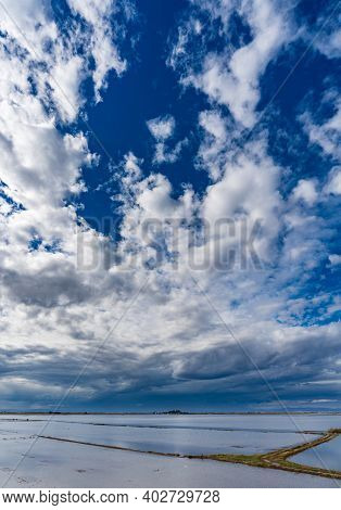 Flooded Rice Fields, Heap And Cloudy Sky