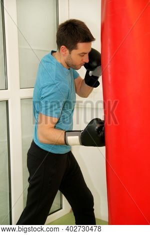 Male Boxer Training Is Exercising With A Punching Bag At The Gym Club. Portrait Of A Young Athlete H