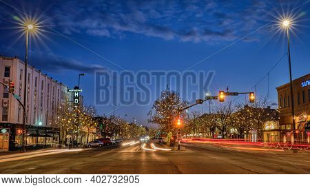 Fort Collins, CO, USA - January 7, 2021: Night cityscape with holiday lights - main street in Fort Collins downtown.