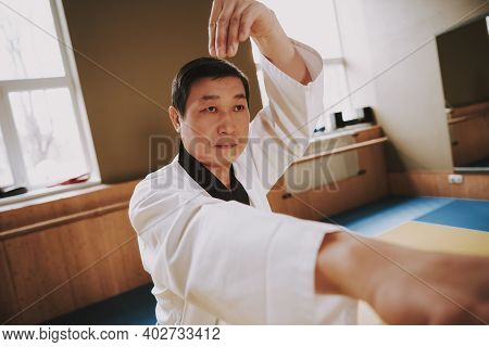 Chinese Adult Man Practicing Karate At Karate School. A Man In A White Kimono Practicing Punches Whi