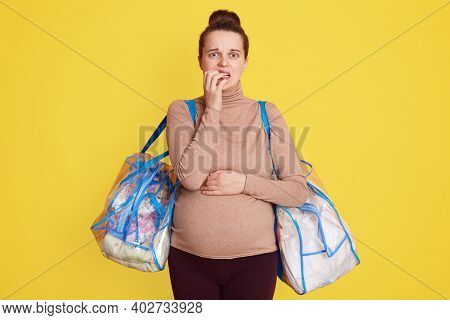 Pregnant Woman Standing Isolated Over Yellow Background Ready To Deliver Going To Hospital, Being Wo
