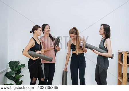Friendly Women Socialising At Yoga Club, Holding Rolled Mats Under Arm