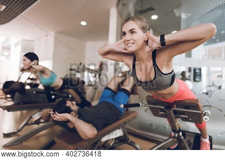 Athletes Engage In Modern Treadmills In The Bright Gym. The Man Kneads The Injured Foot Of A Woman.