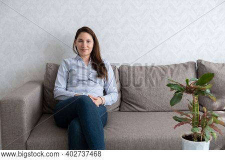 A Young Beautiful Woman In A Blue Shirt And Jeans Is Sitting On The Couch And Looking At The Camera.