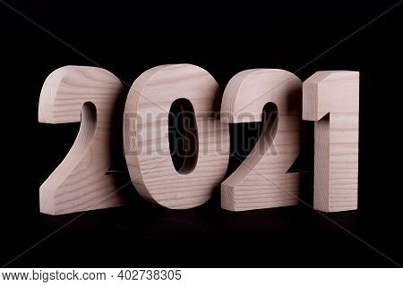 2021 Year Large Wooden Numbers Overlapping. Hardwood Characters On A Black Background