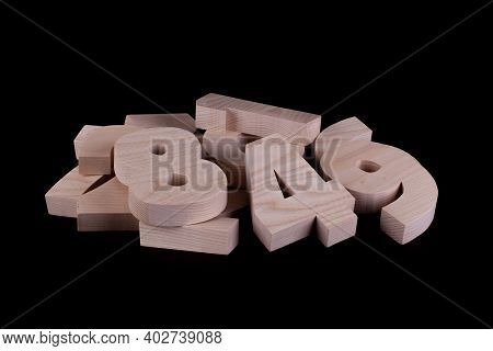 Pile Of Large Random Wooden Numbers With A Black Background. Hardwood Cutout Shapes