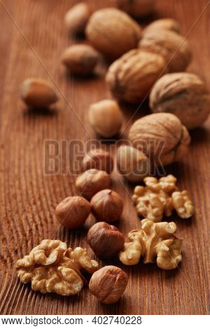 Walnuts and hazelnuts. Still life from whole nuts and kernels on brown textured wooden background. Selective focus on kernels. Healthy food. Vegetarian food
