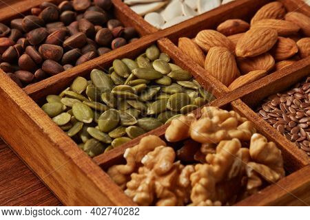 Various varieties of nuts and dried seeds lying in wooden box on brown wooden background. Top view. Healthy food. Vegetarian nutrition. Selective focus on pumpkin seeds