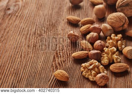 Different kinds nuts. Various varieties of  whole nuts and kernels on brown textured wooden background with copy space. Selective focus on kernels. Healthy food. Vegetarian food