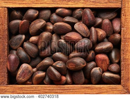 Pine nuts in wooden box on brown wood background. Pinus sibirica, siberian pine nuts. Top view. Healthy food. Vegetarian nutrition