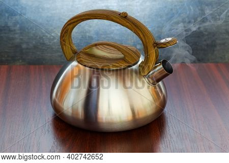Stainless Steel Stovetop Kettle With Open Steam Whistle On Spout Filled With Boiling Water On A Wood