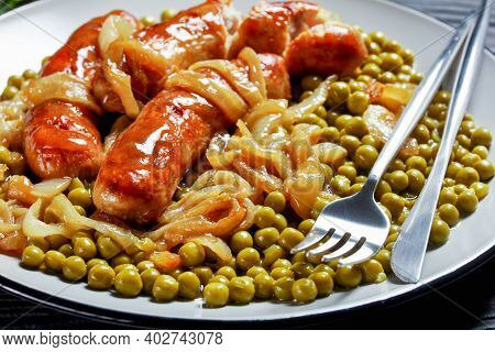 Breakfast Meal: Pork Sausage With Green Peas And Classic Onion Gravy On A Plate With Cutlery On A Da