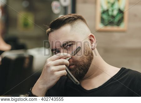 Sexy Handsome Bearded Man Holding A Straight Razor While Standing At The Barbershop. Straight Razor,