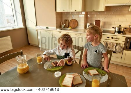 Little Children Having Breakfast On Their Own In The Morning At Home. Adorable Girl Watching Her Bro