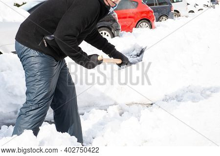 Caucasian Man Equipped With Snow Clothing And Footwear Helps Shovel Snow From A Snow-covered Public