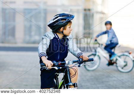 Two School Kid Boys In Safety Helmet Riding With Bike In The City With Backpacks. Happy Children In